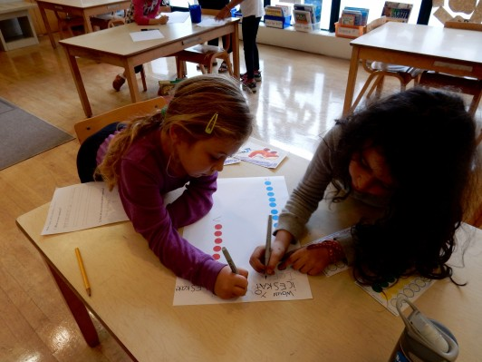<em>Students working to create a poster representing their results.</em>