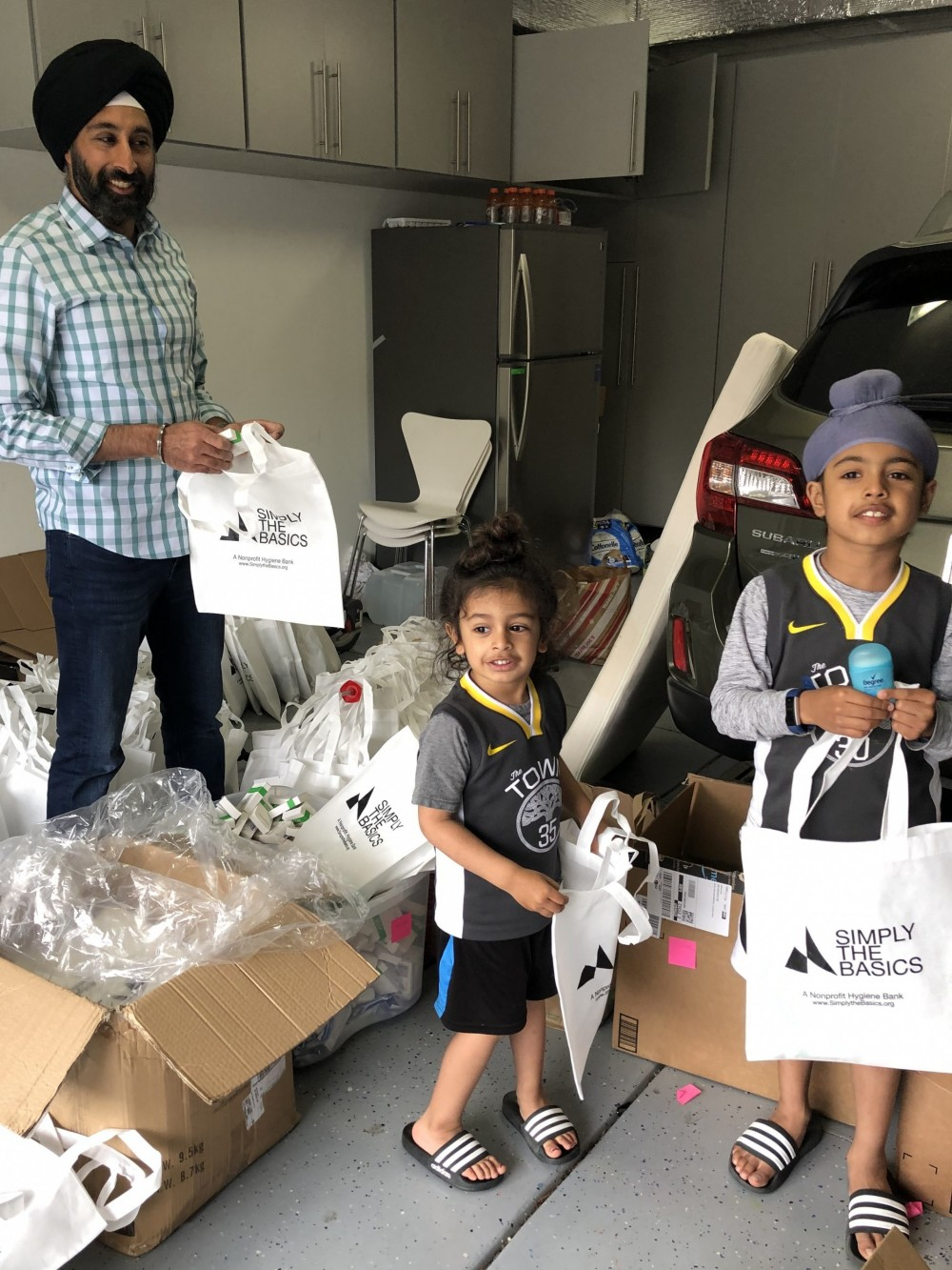 Baljeet Singh, Trustee and Parent, prepares hygiene kits with his sons for delivery to Simply the...