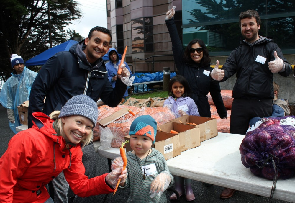 Preschool and Elementary School families distribute carrots on a rainy morning at the Excelsior C...